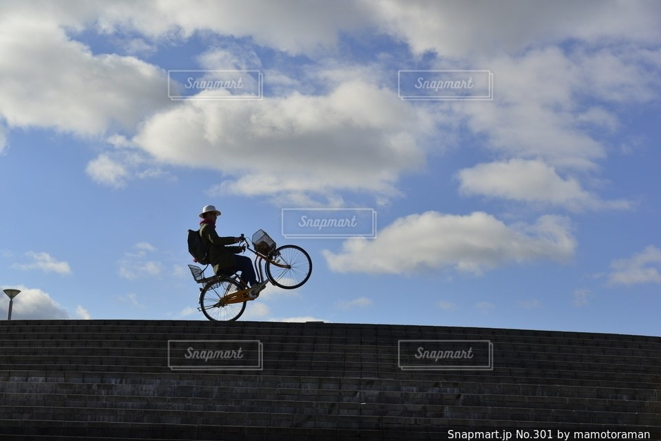 曇りの日に自転車に乗りながら空気を通って飛んで男 - No.301