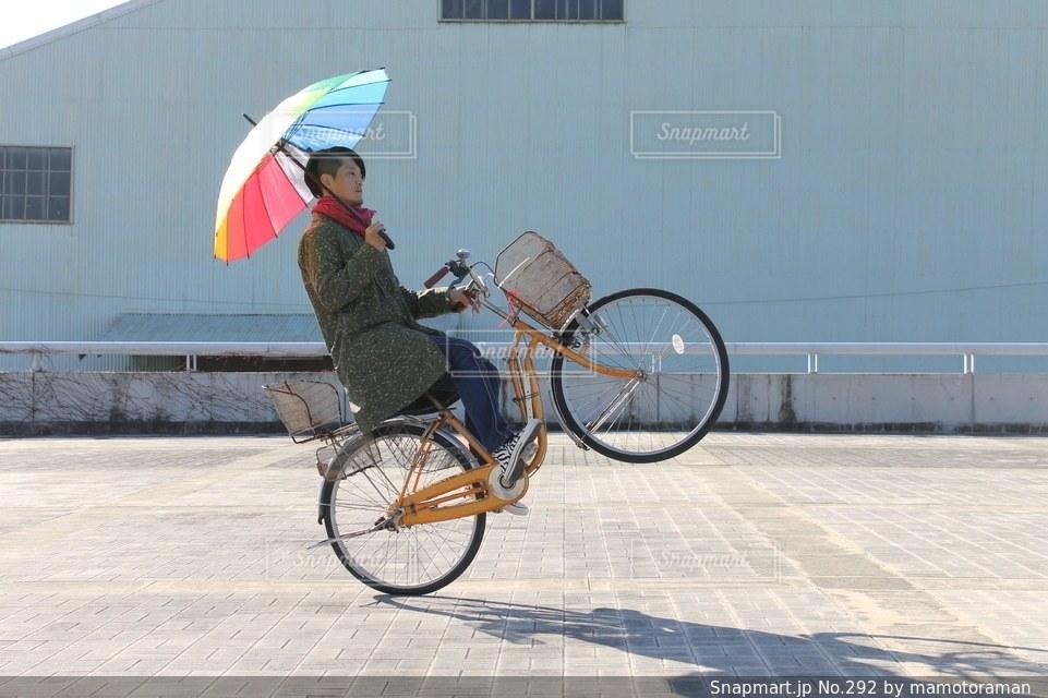 建物の前で自転車に乗る男 - No.292