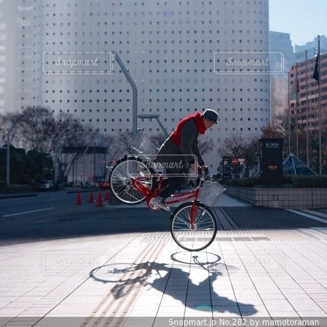 建物の前で自転車に乗る男の写真・画像素材[282]