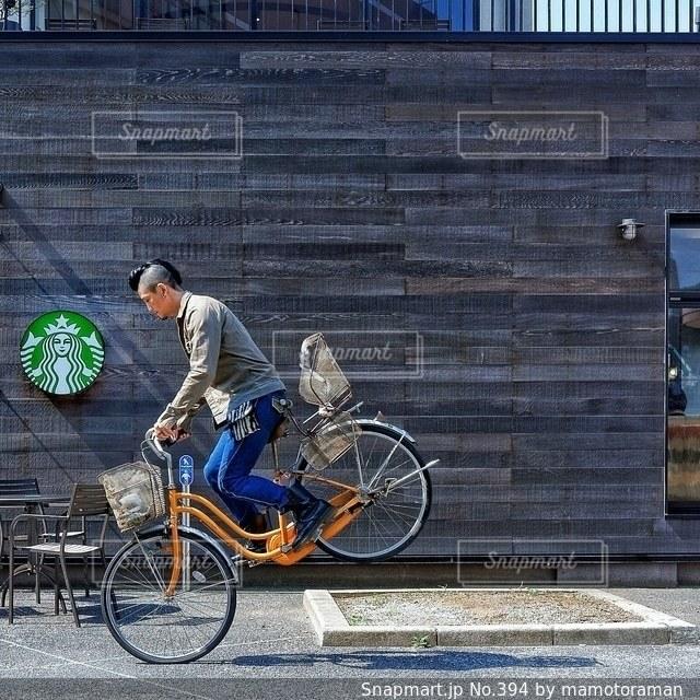 建物の前で自転車に乗る男 - No.394