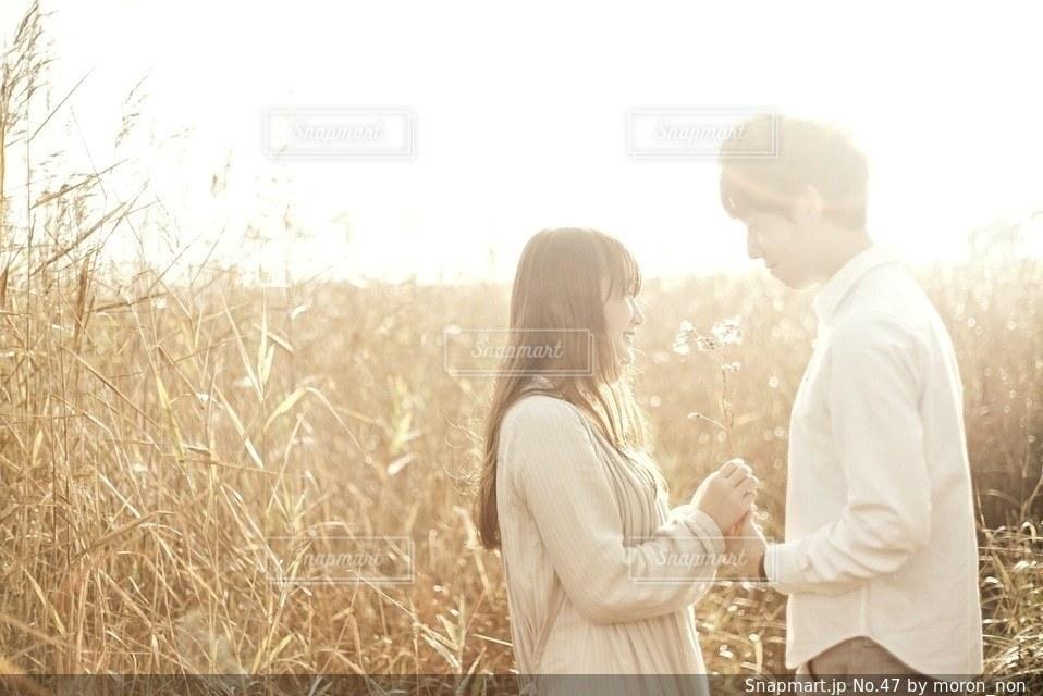 男と女の草の中に立っています。 - No.47