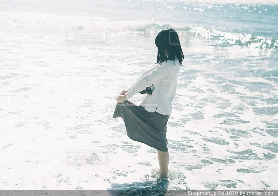 水の体の横に立っている女性の写真・画像素材[1070]