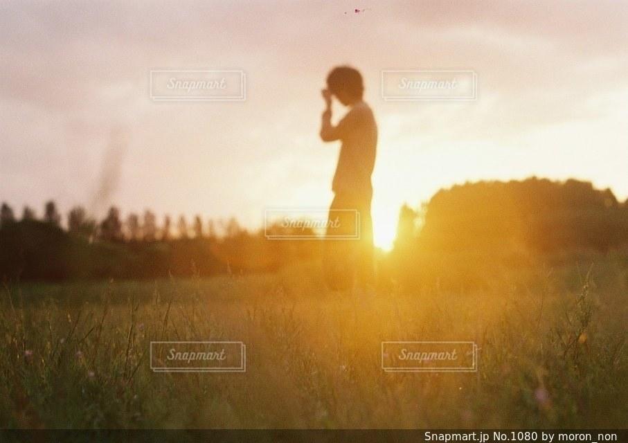 日没の前に立っている男の写真・画像素材[1080]
