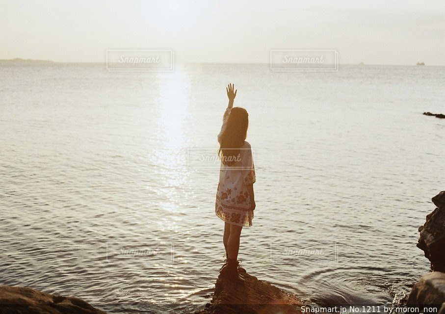 水の体の横に立っている人の写真・画像素材[1211]