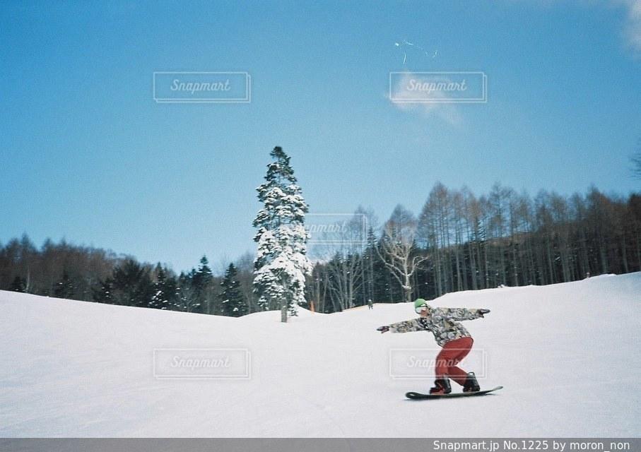 雪をスノーボードに乗る男覆われた斜面 - No.1225