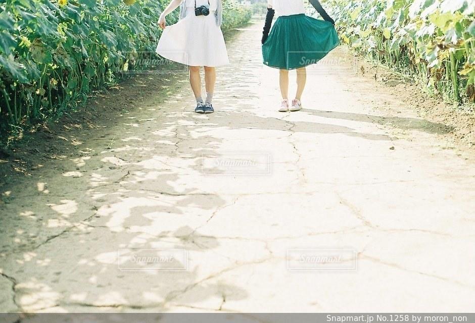傘を保持している未舗装の道路を歩いて女性の写真・画像素材[1258]