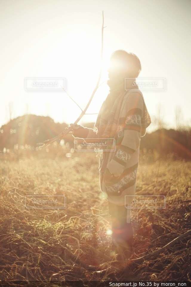 バック グラウンドで夕日を持つ男の写真・画像素材[35]