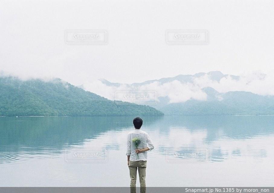 水の体の横に立っている人の写真・画像素材[1385]