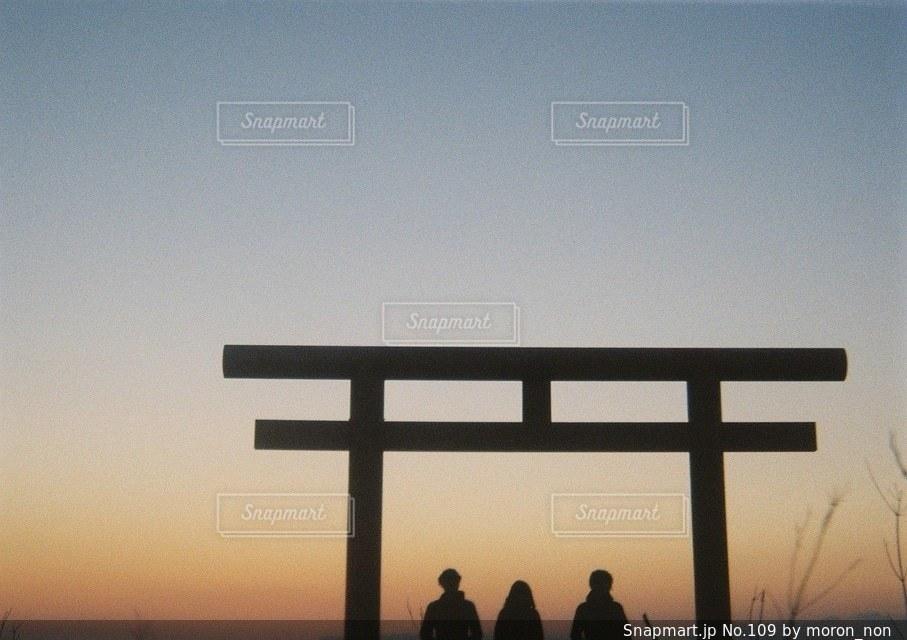 バック グラウンドで夕日を持つ男の写真・画像素材[109]