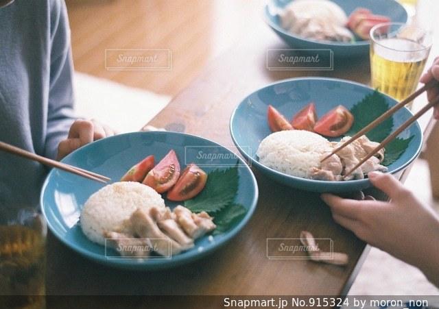 食品のプレートをテーブルに着席した人の写真・画像素材[915324]