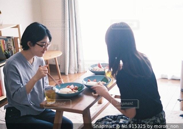 テーブルに座っている人々 のグループの写真・画像素材[915325]
