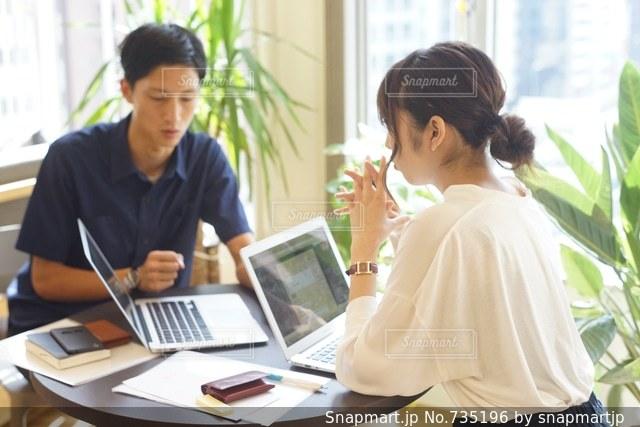 ラップトップ コンピューターを使用してテーブルに座っている人々 のグループの写真・画像素材[735196]