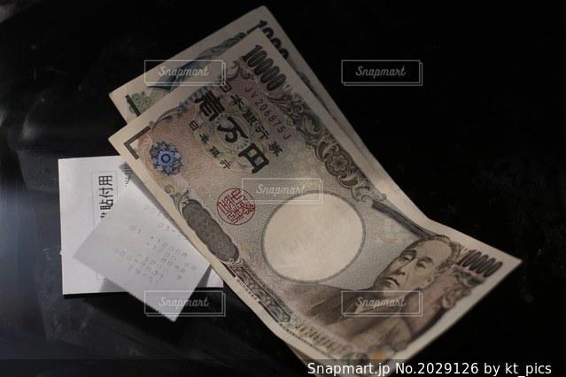 レシート、領収書と現金紙幣。千円札と一万円札。どうなる日本の今後、消費増税、キャシュレス化の波の写真・画像素材[2029126]