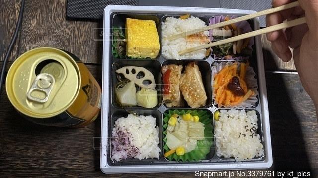 異なる種類の食べ物が入った弁当と缶ビールの写真・画像素材[3379761]
