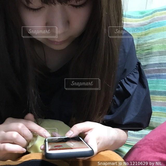 女性の携帯電話を使用しての写真・画像素材[1210629]