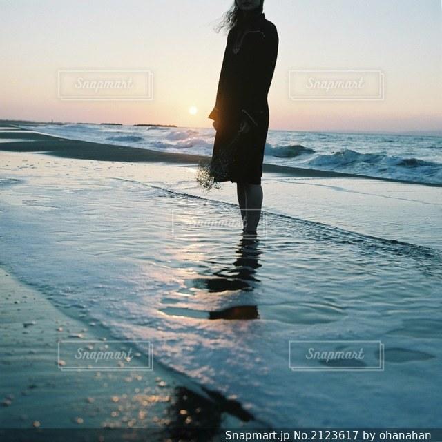 水域の隣に立っている男の写真・画像素材[2123617]