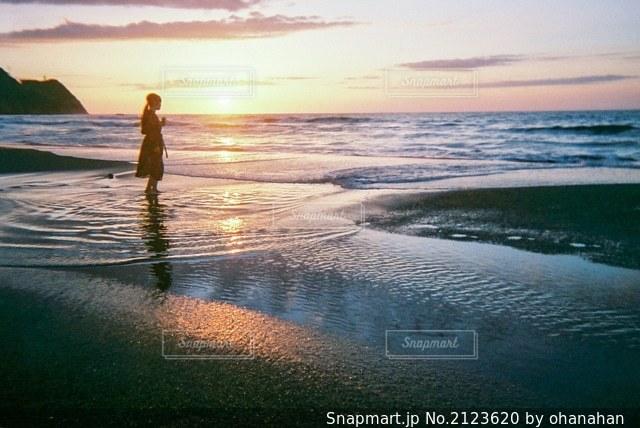 濡れたスーツを着て浜辺に立っている男の写真・画像素材[2123620]