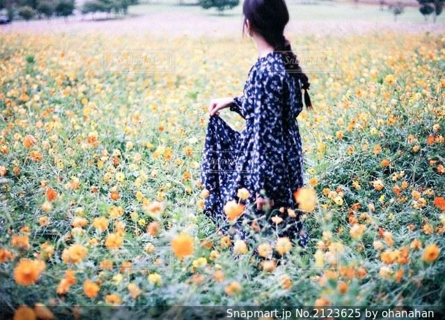 花の野原を持っている人の写真・画像素材[2123625]