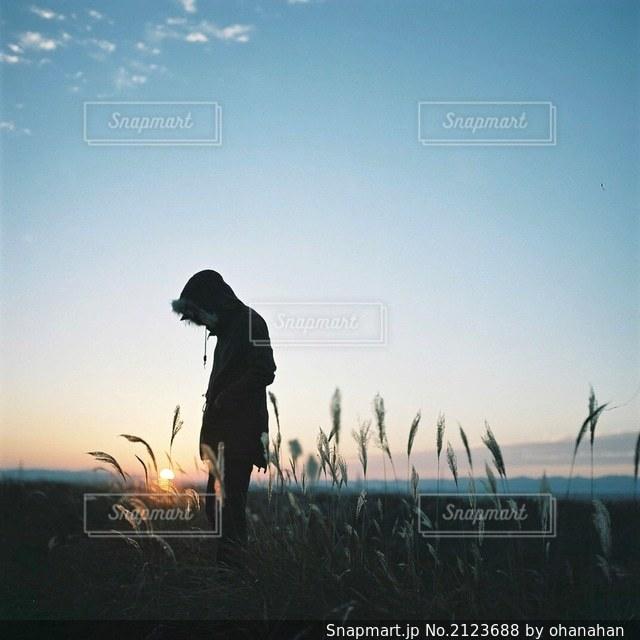 日没の前に立っている人々のグループの写真・画像素材[2123688]