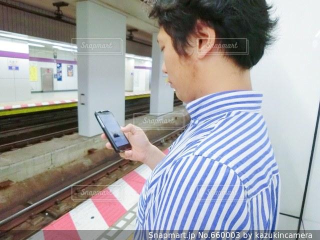 駅ホームでスマホ操作する男性の写真・画像素材[660003]