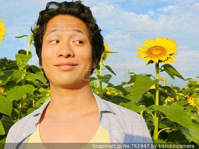 黄色の花の前でカメラにポーズ人の写真・画像素材[761947]