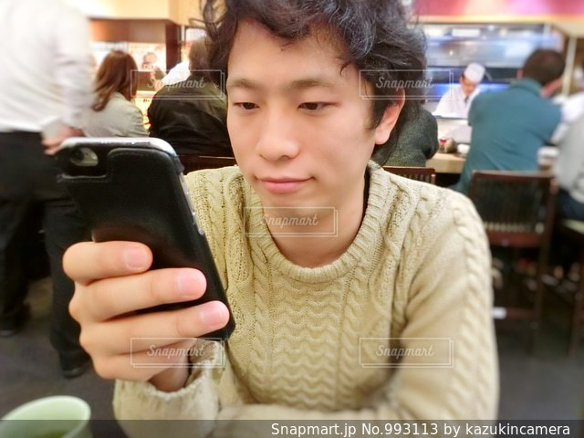 テーブルの上に座って若い男の写真・画像素材[993113]