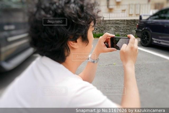 携帯電話で写真を撮る男性の写真・画像素材[1167626]