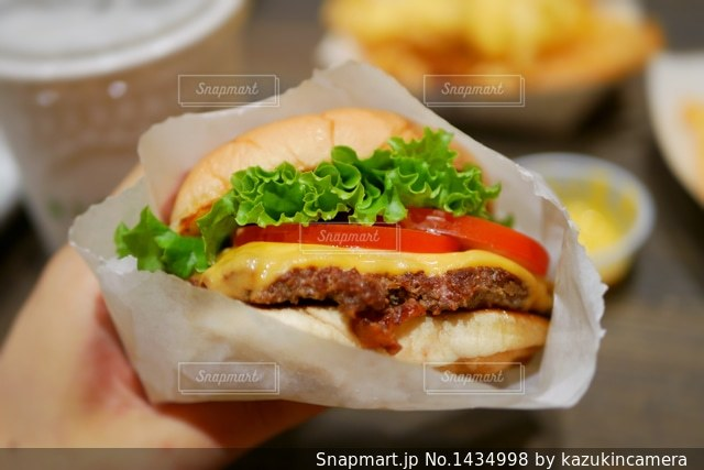 手に持つハンバーガーのアップの写真・画像素材[1434998]