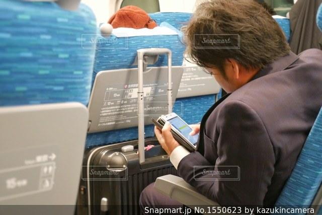 スーツケースを持つ新幹線に乗った男性の写真・画像素材[1550623]