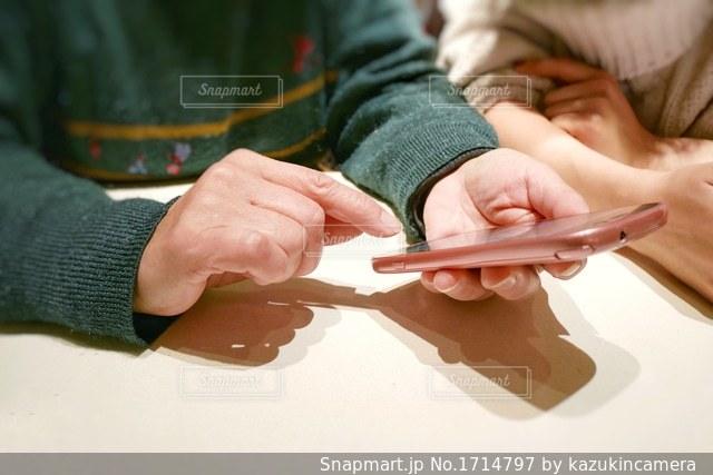 テーブルに座ってスマホ操作について話す2人組の写真・画像素材[1714797]