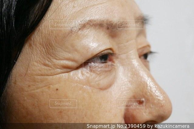目尻のシワがある年配の女性の写真・画像素材[2390459]