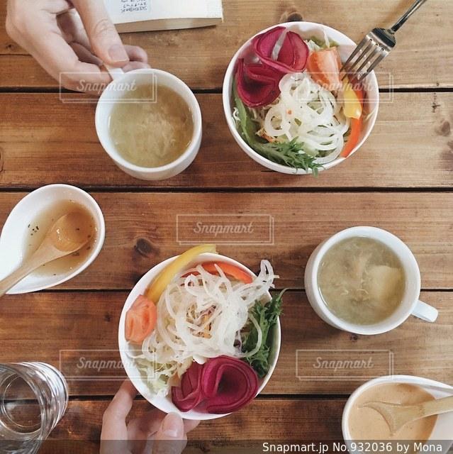 食品や木製のテーブルの上のコーヒー カップのプレートの写真・画像素材[932036]