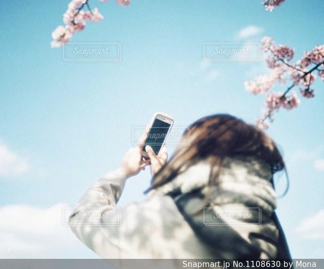 スマホで写真を撮る女性の写真・画像素材[1108630]