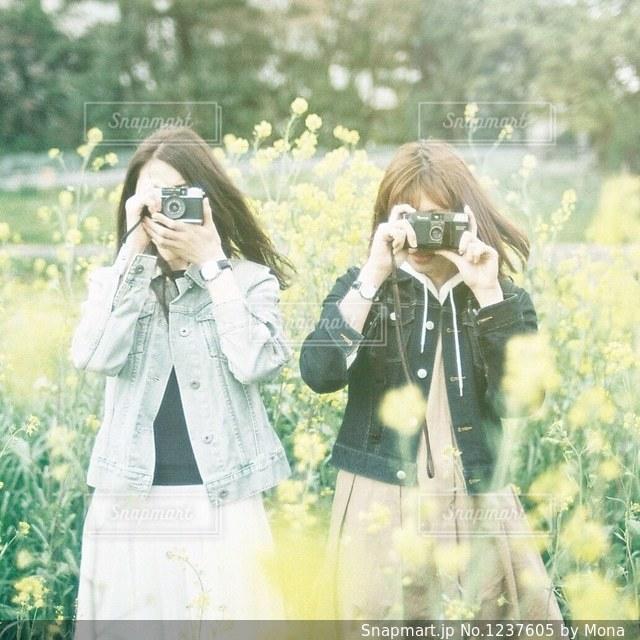 菜の花畑のカメラ女子たちの写真・画像素材[1237605]