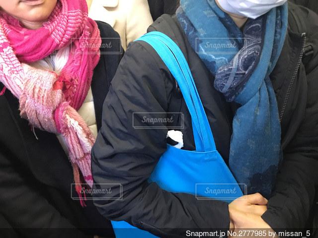 寒い冬の朝、マフラーを巻いて通勤電車に乗る大人の女性の写真・画像素材[2777985]