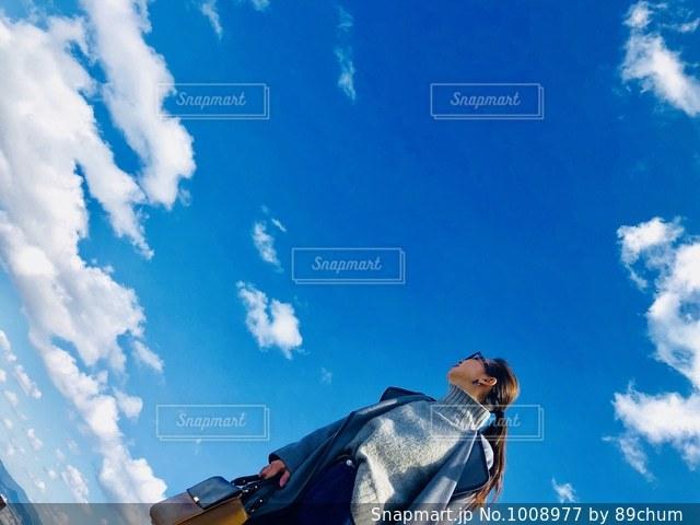 青い空を飛んでいる人の写真・画像素材[1008977]