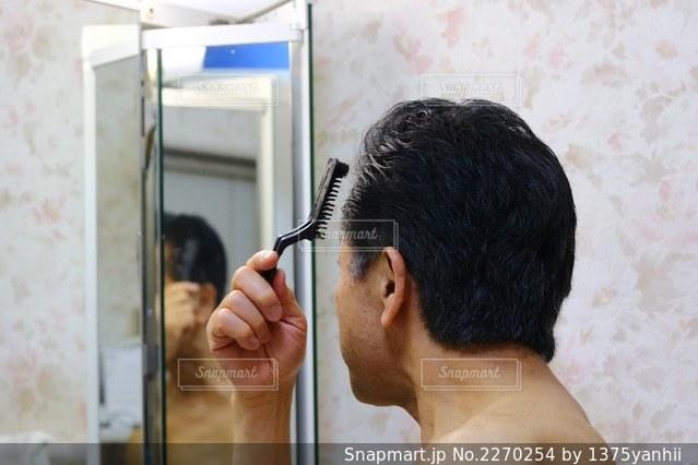 鏡の前に立つ男がカメラに向かってポーズをとるの写真・画像素材[2270254]