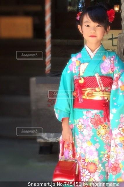 建物の前に立っている赤いドレスを着ている男の子の写真・画像素材[745450]
