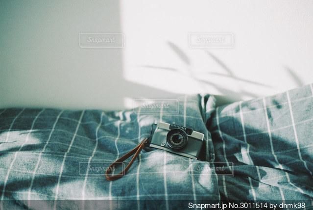 枕元のカメラと朝の光の写真・画像素材[3011514]