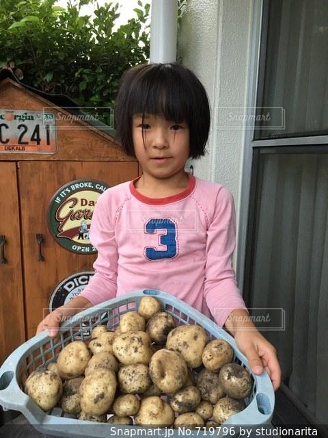 食品のプレートの前に立っている女の子の写真・画像素材[719796]