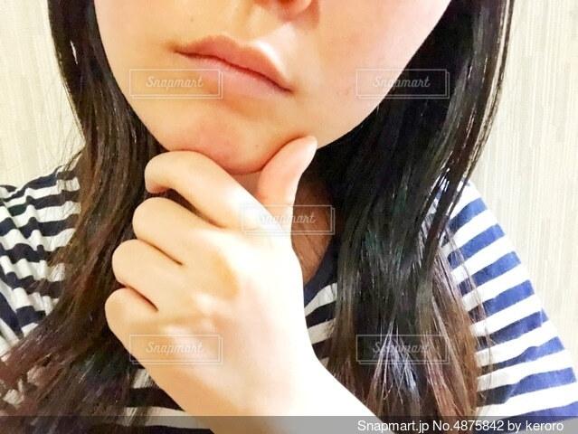 悩んでいる女性の顔の写真・画像素材[4875842]