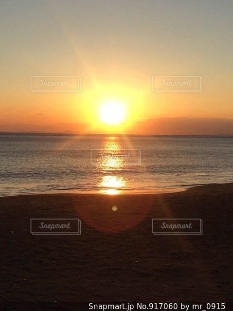 海の横にあるビーチに沈む夕日の写真・画像素材[917060]