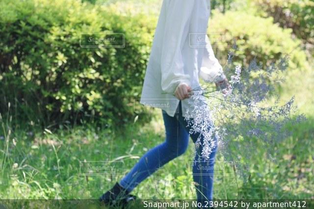 花を持って草の上を歩くジーンズを履いた女性の写真・画像素材[2394542]