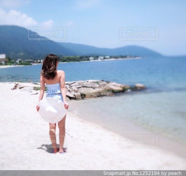 水の体の近くのビーチに立っている女性の写真・画像素材[1252194]