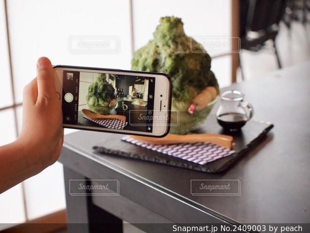 ノートパソコンの前のテーブルに座っている人の写真・画像素材[2409003]