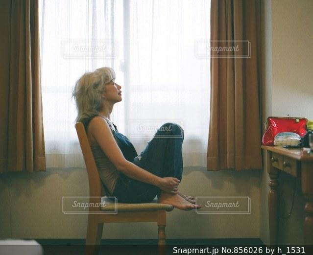 カーテンの前に座っている女性の写真・画像素材[856026]