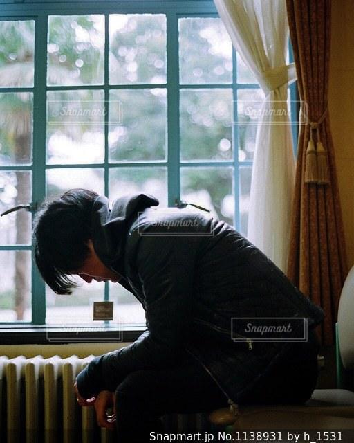 窓際に座る男の人の写真・画像素材[1138931]