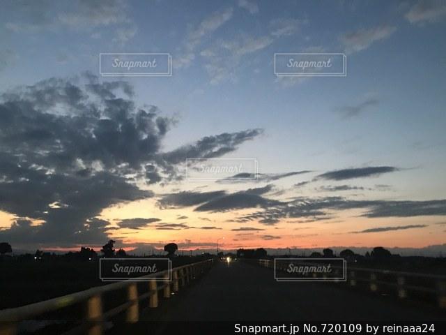 バック グラウンドで市と水体に沈む夕日の写真・画像素材[720109]