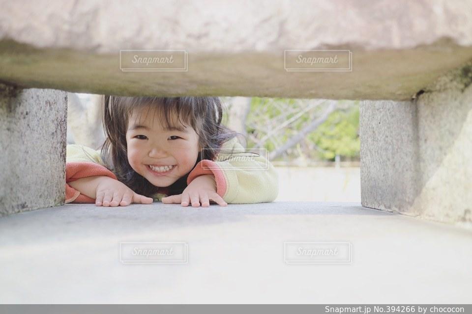 1人,かわいい,スマイル,女子,女の子,楽しい,嬉しい,隙間,笑顔,幸せ,幼児,石,明るい,覗く,コピースペース,笑う,2歳
