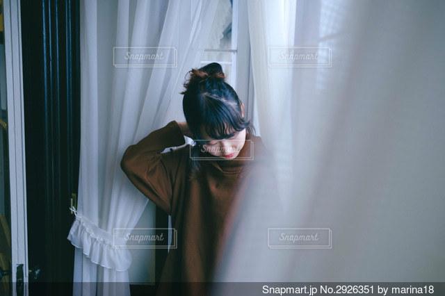 カーテンの前に立っている人の写真・画像素材[2926351]